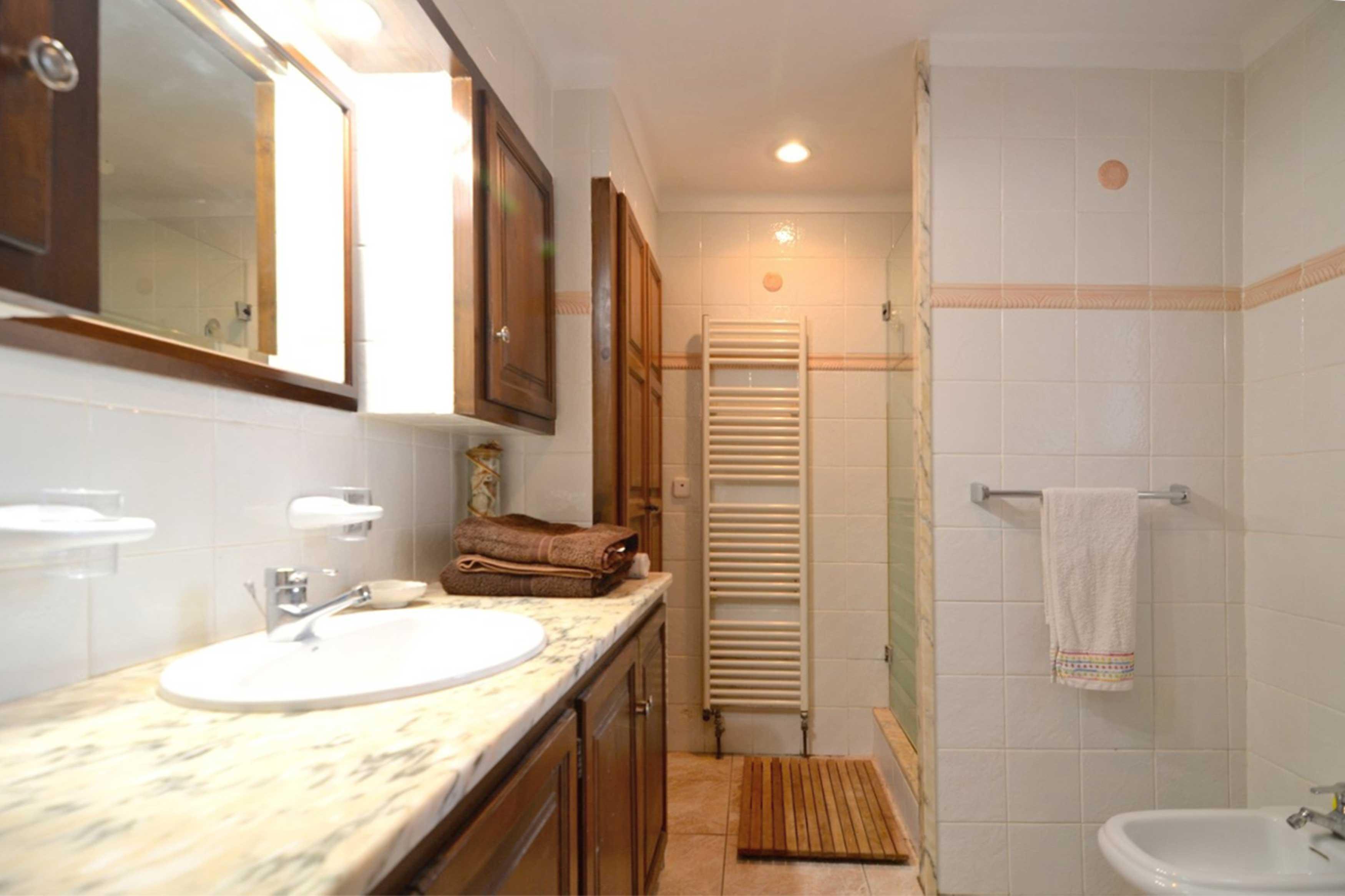 Badkamer met douche en wasbak bij villa Buckingham